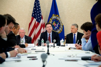 FBI Director James Comey, flanked by 9/11 panel members Ed Meese, left, and Tim Roemer with reporters at March 25 press conference