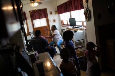 Sylvester and Gladys Clayborn sit in their kitchen as their granddaughters and great niece play nearby. The couple fell into debt when Gladys was permanently disabled after heart surgery. Photo: Edwin Torres/ProPublica