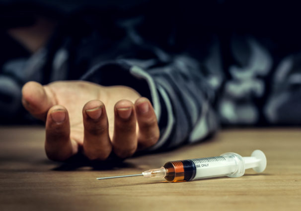 a syringe lying next to a dead man's outstretched hand